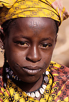 Delaquara, Niger. Young Fulani Woman with Prominent Facial Scarification, wearing Cowrie Necklace.  Facial scarification--the cutting or tattooing of designs or patterns into the face--is still practiced in traditional communities of West Africa. This young woman of the Fulani tribe bears the typical tattoos and facial markings of the Fulani tribe of southern Niger. This custom probably originated in a time when tribal raiding and kidnapping was common. It offered an indelible way of establishing a person's tribal identify in the event opportunities should arise for recapturing victims of earlier kidnapping. The practice continues today because of the force of tradition, because people are proud of their tribal affiliation, and because the marks are regarded as a sign of beauty or attractiveness. .