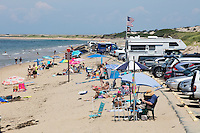 People sit on the beach near cars in the parking lot at Herring Cove Beach in the Cape Cod National Seashore outside of Provincetown, Mass., USA, on Fri., July 1, 2016. Portions of the parking lot have been closed after land eroded during storms earlier this year.