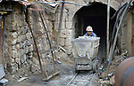 A miner pushes an ore cart out of a mine in Potosi, Bolivia. The mine produces silver and other metals.