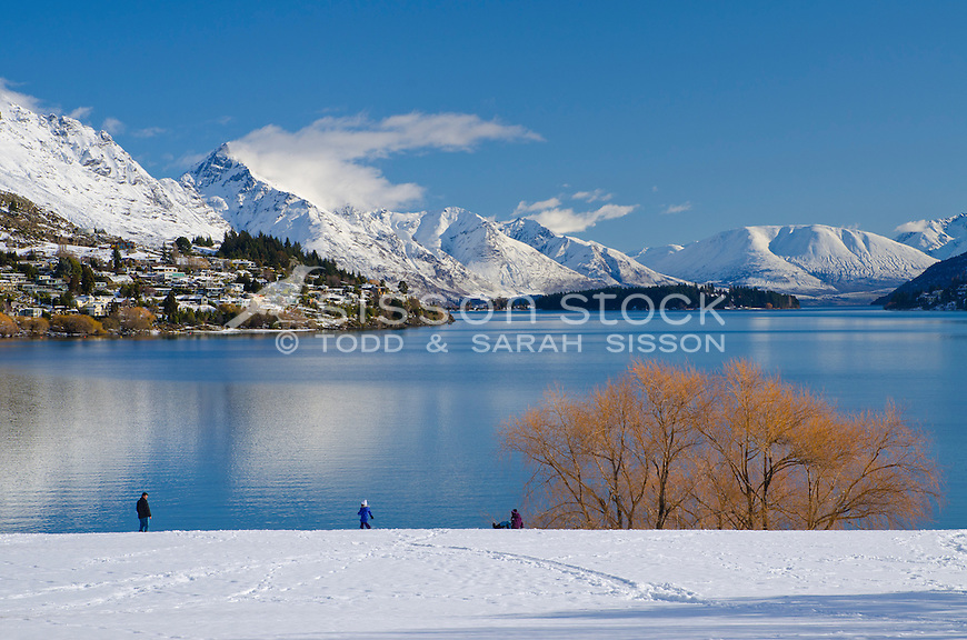 Looking down Lake Wakatipu towards snow covered Queenstown, Kelvin Heights, Walter and Cecil Peaks on a sunny winter's day from Frankton, South Island, New Zealand