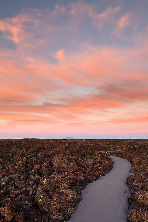 A pathway vanishes into the sunset at Craters of the Moon National Monument.