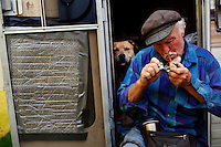 """Ventura, California, July 21, 2010 - A portrait of Gary Seymour with his Staffordshire terrier, Buddy, at their home, a camper parked left to him by his father that is parked in the driveway of a friend's mother. Because it is an illegal camp, Mr. Seymour is considered homeless. Mr. Seymour has been homeless off and on for the last thirty years. He says, """"I work odd jobs, landscaping and whatnot to make a little money. I am trying to get back on my feet."""" Mr. Seymour is proud that he does not panhandle. """"I earn my own living without asking people for handouts."""" .."""
