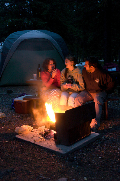 Willow Feeley, Audrey West and Milos Radovanovic enjoy a campfire in front of their tent, Sept. 14, 2008, in Denali National Park's Riley Creek Campground.