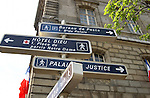 Signs pointing to various destinations in Paris outside government building.