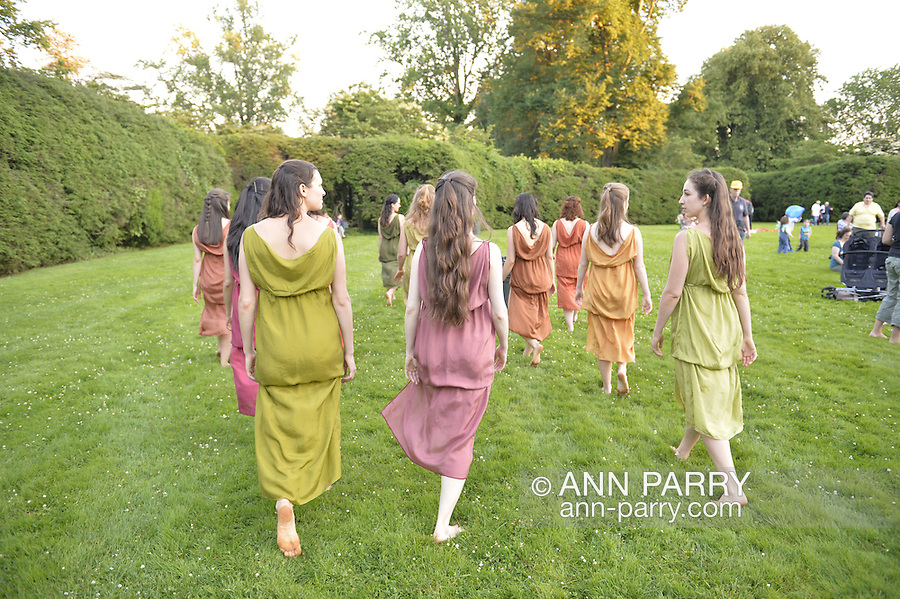 Old Westbury, New York, U.S. - June 21, 2014 - Lori Belilove & The Isadora Duncan Dance Company dances modern dance in Greek tunics throughout the gardens during the Midsummer Night event at the historic Long Island Gold Coast estate of Old Westbury Gardens on the first day of summer, the summer solstice. Ms. Belilove is wearing a Greek white tunic and purple over-scarf.