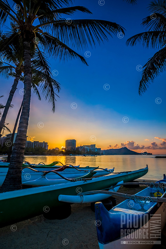 Sunrise in Waikiki, with outrigger canoes in the foreground and Diamond Head in the distance, Honolulu, O'ahu.