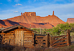 Castle Valley, Grand County, UT<br /> Weathered log shed and fence on Castle Valley ranch with background view of Castleton tower and the Rectory towers