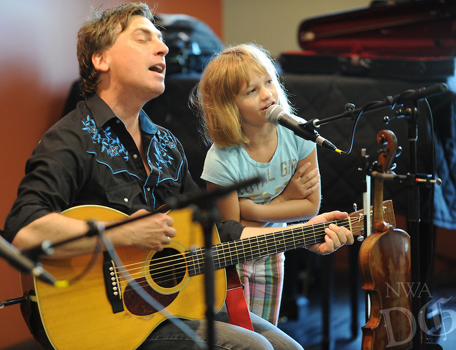STAFF PHOTO ANDY SHUPE - Joe Crookston of Ithaca, Ny., performs alongside Ashley McClelland, 8, of Fayetteville Wednesday, July 9, 2014, during a concert for kids at the Fayetteville Public Library. Crookston will perform at 10:30 a.m. today at a family concert and conduct songwriting workshops during the day before hosting a culminating concert at 6:30 p.m. A concert is also planned for 7 p.m. Friday.