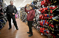 NWA Democrat-Gazette/DAVID GOTTSCHALK Officer Cary Bostian, with the Springdale Police Department, shops Tuesday, December 4, 2018, with Tiki Lanki, 11, at the Walmart Supercenter on Pleasant Street in Springdale. More than 200 children participated in the Springdale Police Department Shop with a Cop program. The department collected $45,000 this year for the program.