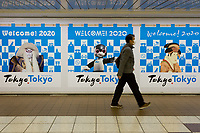 A Japanese man, wearing a paper face mask, walks past posters welcoming people to Tokyo for the 2020 Olympics. Shinjuku Station, Tokyo, Japan, Thursday February 27th 2020. The Corona Virus pandemic, also know COVID-19, that started in China at the end of 2019, has been handled ineptly in Japan and there are fears that the summer Olympics will be cancelled unless the outbreak can be brought under control quickly.