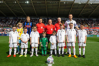 Mike van der Hoorn of Swansea City with mascots during the Sky Bet Championship match between Swansea City and Rotherham United at the Liberty Stadium in Swansea, Wales, UK.  Friday 19 April 2019