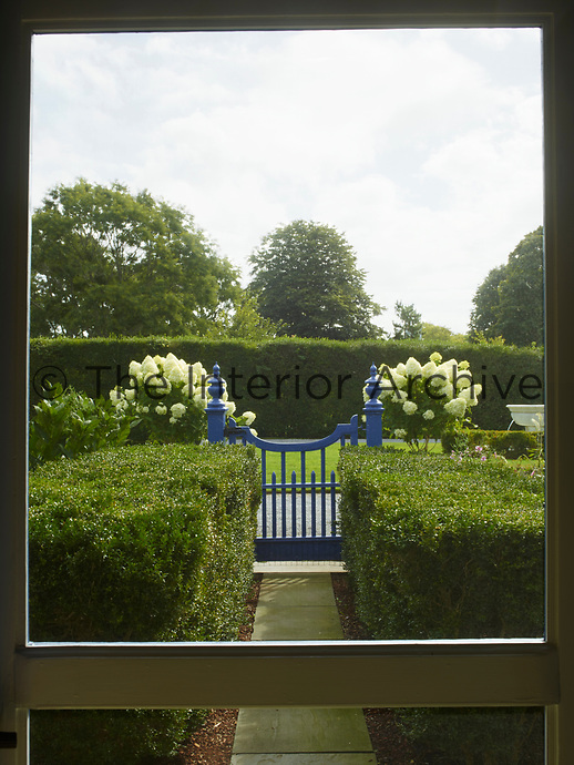 The front garden seen through the door screen; the front path leads down to a blue painted gate.
