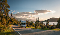 Campervan on road at Lake Ianthe at sunset, West Coast, South Westland, South Island, New Zealand