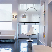 An 'Arco' lamp curves over a white 'Statuette' chair by Lloyd Schwan in a corner of the home office/meeting room