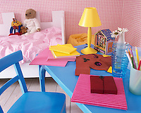 A child's bedroom with pink gingham check wallpaper and matching beddiing. A yellow lamp stands on a blue painted table.