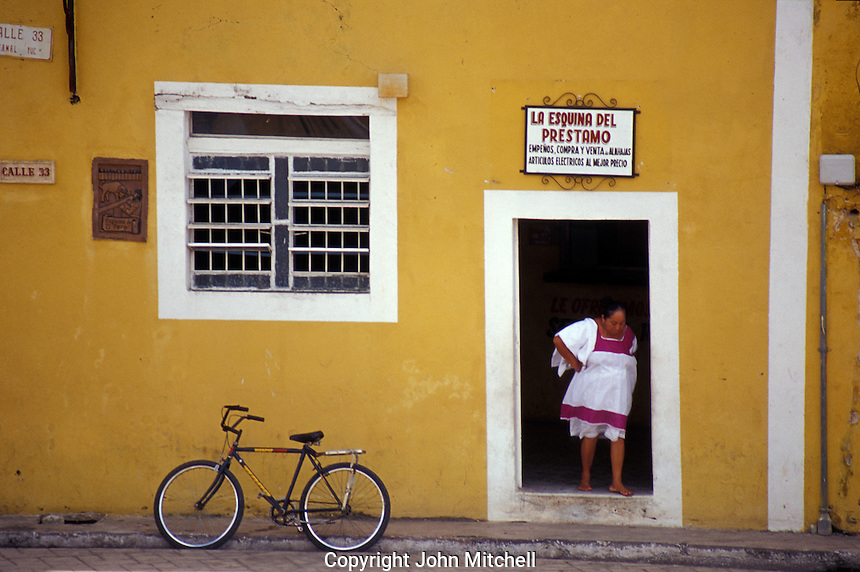Maya woman standing in a doorway in the Spanish colonial town of Izamal, Yucatan, Mexico