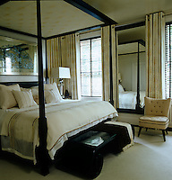 The bedroom windows are dressed with black Venetian blinds and thick cream curtains on chrome poles