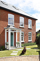 The exterior of Jo Burns's and Sharon Lillywhite's idyllic Bedfordshire home, with Paddy, their 10 year old chocolate labrador sitting on the lawn