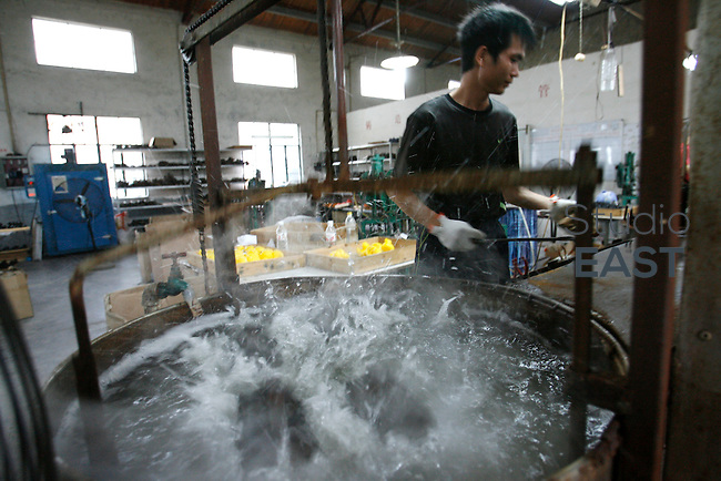 A worker plunges newly-molded bath ducks in water to cool them off, in a factory in Fengxiang, near Shanghai, China, on October 30, 2008. Although Chinese authorities predict that 2009 will be a tough year, they are ready to do all that is takes to keep China's growth ''around 8%''. Beijing government announced a 450 billion euros investment plan until 2010 to boost Chinese economoy. ''We could take new measures (...) to prevent any economical downturn'' said Premier Wen Jiabao in Davos 2009 economy forum. Photo by Lucas Schifres/Pictobank