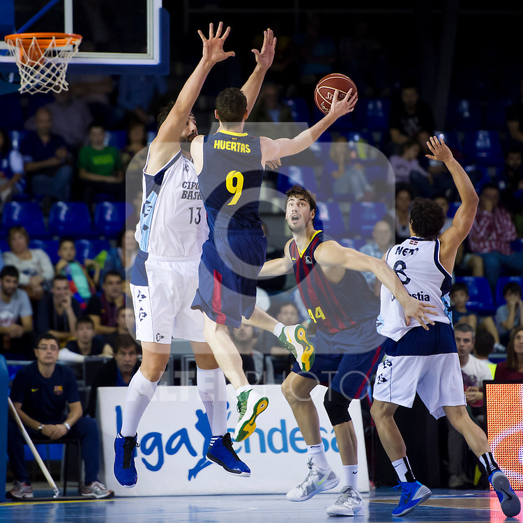 FC Barcelona's Marcelinho Huertas (2nd left) tries a pass to Ante Tomic (2nd right) with the opposition of Gipuzkoa Basket Club's David Doblas (left) and Raul Togni Neto (right) during Liga Endesa ACB 2013-2014 match. November 3, 2013. (ALTERPHOTOS/Alex Caparros)