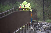 Taylor Murphey (cq) (right) and Jonathan Chick, both with the United States Geological Survey, prepare to take a sample Thursday, March 19, 2020, from a bridge on the Razorback Greenway over Clear Creek in Johnson. The survey monitors several creeks and waterways including taking storm event samples. Check out nwaonline.com/200320Daily/ and nwadg.com/photos for a photo gallery.<br /> (NWA Democrat-Gazette/David Gottschalk)