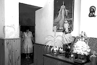 """Initiates of the Umbanda religion take part in a spiritual session at Mae Susana's temple in Montevideo Uruguay. A Paint wit the image of Yemanja the """"Goddess of the Sea"""" is seen on the wall. Cults such as Umbanda worship deities called Orixas, including Yemanja, who have spiritual dominion over elements of nature such as fire and water. Photo by Quique Kierszenbaum"""