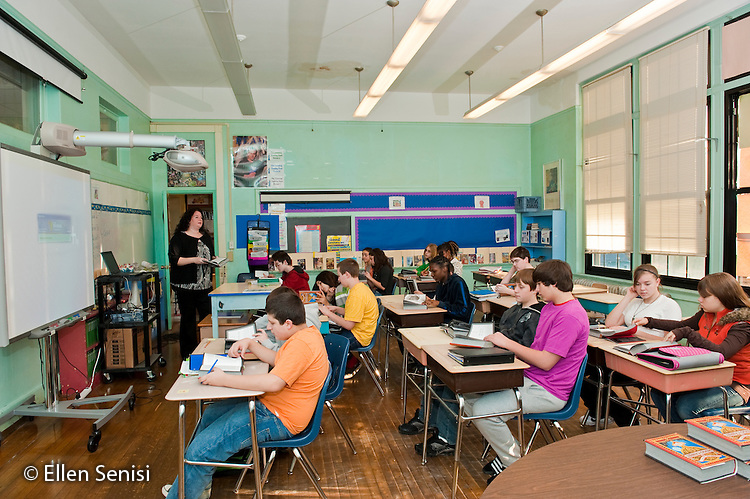 "MR / Schenectady, New York. Oneida Middle School (urban public school). 8th grade English class. One of a series of photographs of a lesson centered around the graphic novel ""The Invention of Hugo Cabret"" by Brian Selznick. Teacher teaching in her classroom as students listen and take notes; digital white board is at left. MR: Bon3. ID: AJ-g8b. © Ellen B. Senisi"