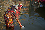 Indian women in traditional dress bathing and making offerings at the Ganges River in Varanasi, Uttar Pradesh, India