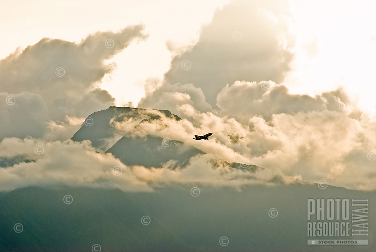Airplane flying through clouds above the west Maui mountains