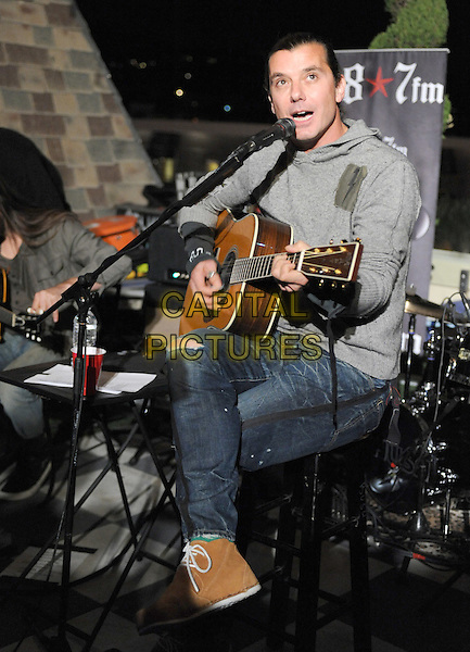 Gavin Rossdale.98.7FM Presents Bush  in an exclusive live performance at the 98.7FM Penthouse inside the Historic Hollywood Tower in Hollywood, California, USA..January 31st, 2012     .on stage in concert live gig performance performing music full length grey gray hooded top singing jeans denim yellow sneakers trainers legs crossed                                                          .CAP/RKE/DVS.©DVS/RockinExposures/Capital Pictures.