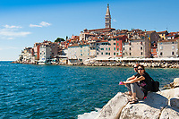 Tourists sit on rocks overlooking the harbour at Rovinj, Istria County, Croatia