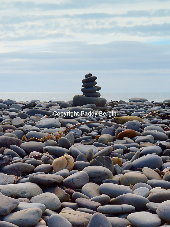 A cairn is a man-made pile (or stack) of stones. The word cairn comes from the Scottish Gaelic: c&agrave;rn. <br /> <br /> Cairns are used as trail markers in many parts of the world, in uplands, on moorland, on mountaintops, near waterways and on sea cliffs, as well as in barren deserts and tundra. They vary in size from small stone markers to entire artificial hills, and in complexity from loose conical rock piles to delicately balanced sculptures and elaborate feats of megalithic engineering.<br /> <br /> A Cairn built from flat pebbles on the West Beach at Aberystwyth.<br /> <br /> Stock Photo by Paddy Bergin.