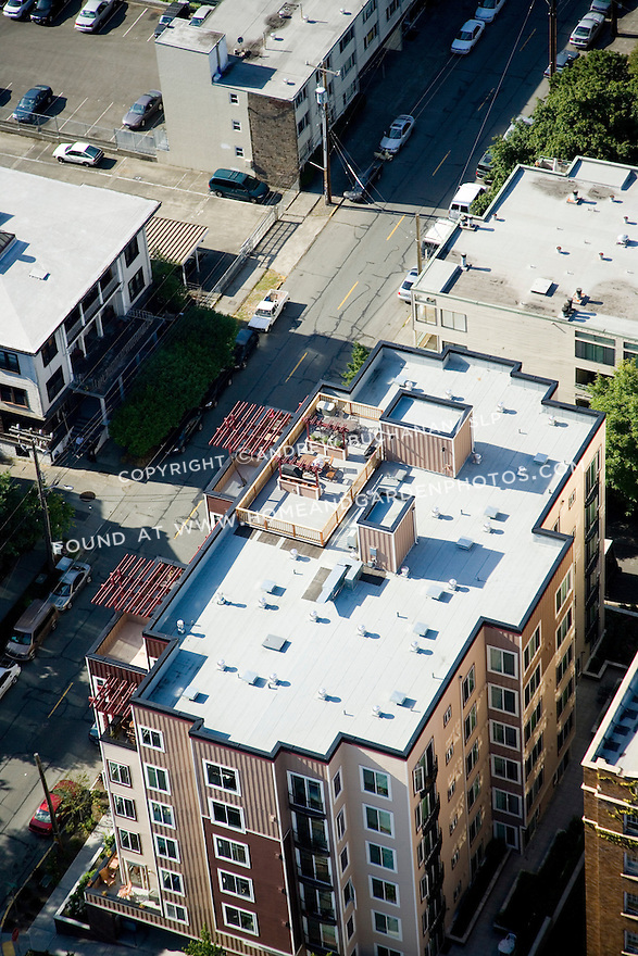 A sunny, summer afternoon aerial photo of Seattle, Washington's Capitol Hill neighborhood showing a rooftop condo garden.