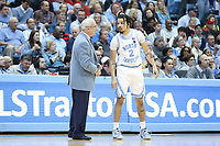 CHAPEL HILL, NC - FEBRUARY 25: Head coach Roy Williams of the University of North Carolina gives instructions to Cole Anthony #2 during a game between NC State and North Carolina at Dean E. Smith Center on February 25, 2020 in Chapel Hill, North Carolina.