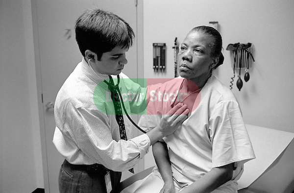 Young male doctor listening with stethoscope on back of older middle age female patient in examination room