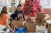 STAFF PHOTO ANTHONY REYES &bull; @NWATONYR<br /> Alexis Samarin, 13, left, and Kassandra Garcia, 12, both students at Tyson Middle School organize donated food Tuesday, Dec. 16, 2014 at the school in Springdale. A few students from Todd Holland's class organized the food to be delivered to local charities. The school collected non-perishable food items to be given to local agencies and families at the school in need.