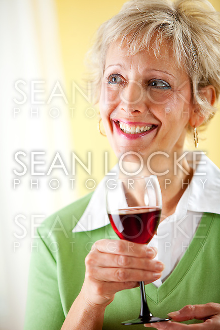 Series with a mature couple, mid 50's, in various themes, including healthy eating, medical and fun.  Isolated on white and an interior room.  Drinking a glass of red wine.