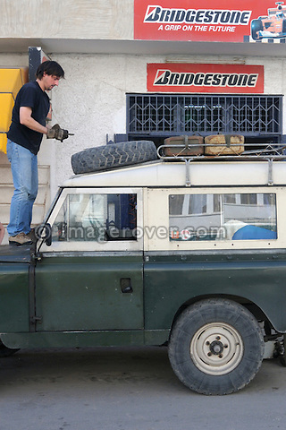 Africa, Tunisia, Nabeul. Traveller undertaking a sahara trip with his historic Series Land Rover refitting the spare tyre after repair at a local tunisian tyre shop. --- No releases available, but releases may not be needed for certain uses. Automotive trademarks are the property of the trademark holder, authorization may be needed for some uses.  --- Info: Image belongs to a series of photographs taken on a journey to southern Tunisia in North Africa in October 2010. The trip was undertaken by 10 people driving 5 historic Series Land Rover vehicles from the 1960's and 1970's. Most of the journey's time was spent in the Sahara desert, especially in the area around Douz, Tembaine, Ksar Ghilane on the eastern edge of the Grand Erg Oriental.