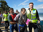 A suspected Turkish migrant smuggler (center) is escorted along a beach near Molyvos, on the Greek island of Lesbos on October 31, 2015. He was rescued from the water after volunteers on the island punctured a raft in which he was trying to flee back to Turkey after depositing a load of refugees. He was turned over to the Greek police.