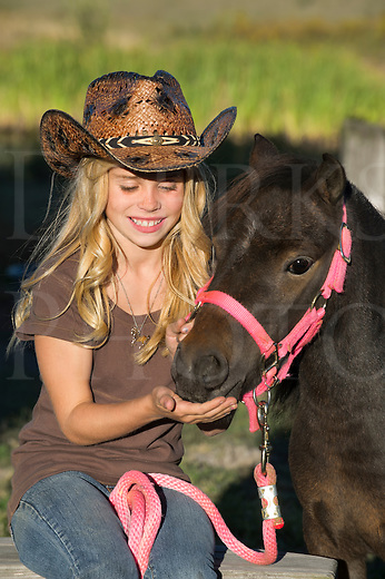 Pretty blonde girl feeds a treat to her miniature horse, portrait of a smiling cowgirl wearing a cowboy hat.