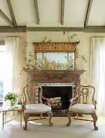 Two Louis VX style armchairs are placed in front of the fireplace, which has a blue and white Delft tile surround and a mirror over mantel. The exposed beamed ceiling and the wallpaper, a faded botanical print which has been bleached by years of bright sun, give the room a rustic feel.