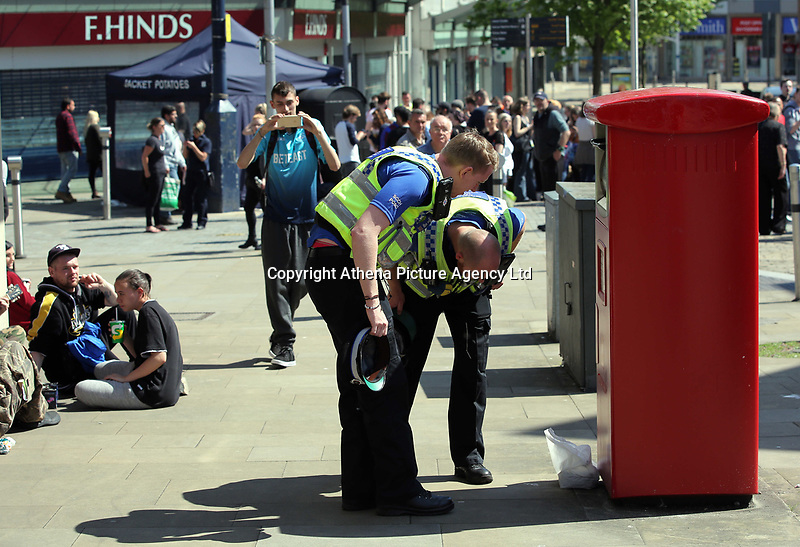 Pictured: Two police officers examine an unattended package left by a post box in Union Street, Swansea Wednesday 24 May 2017<br />