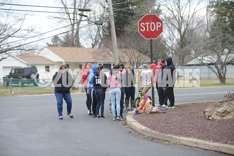 Family and friends gather around a memorial at the site of a fatal ATV crash that left one boy dead and another in critical condition Saturday, January 27, 2017 in Bensalem, Pennsylvania. (Photo by William Thomas Cain)