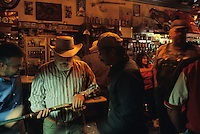BASIN - 2003: At the Silver Saddle Bar, patron Stewart Andrews inspects a special edition Winchester rifle. (photo by Landon Nordemam)