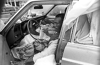 New York, NY - Circa 1989 -- After the City bulldozed a Shanty Town, just off the West Side Highway and  south of the 34th street Heliport, at dawn, these homeless men moved into an abandoned car seeking shelter against the snow storm. Officials cited concerns that the tents and tarmacs might get caught up in helicopter blades. This land has since been developed and is now part of Hudson River Park.