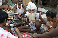 An old man with an impressive beard is squeezed with his companions into a bicycle trailer at the flower market in Kolkata (Calcutta), India, so that they can play cards.