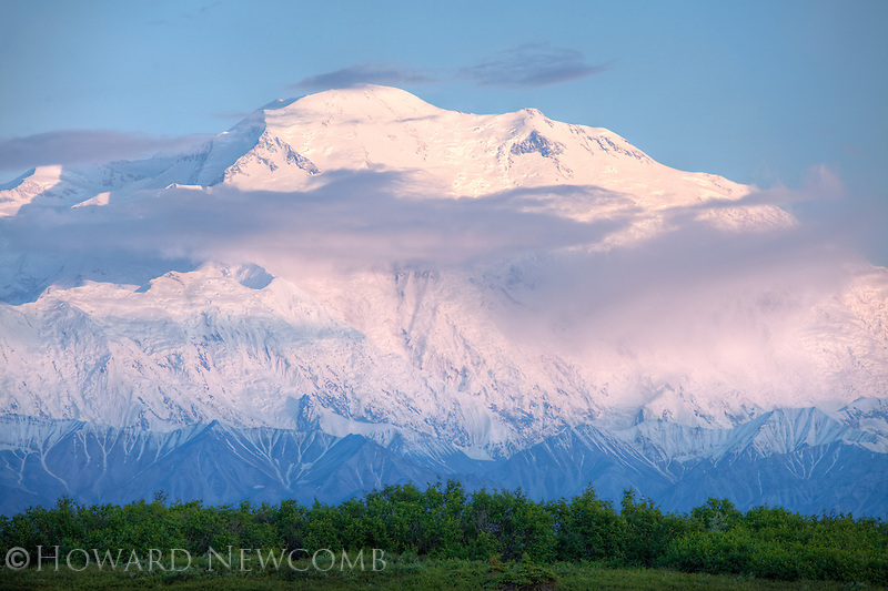 The tallest mountain in the United States, Mount McKinley (20,320') glows softly from the midnight summer sunset.  Denali National Park, Alaska.  Details of the landscape are preserved using HDR processing.