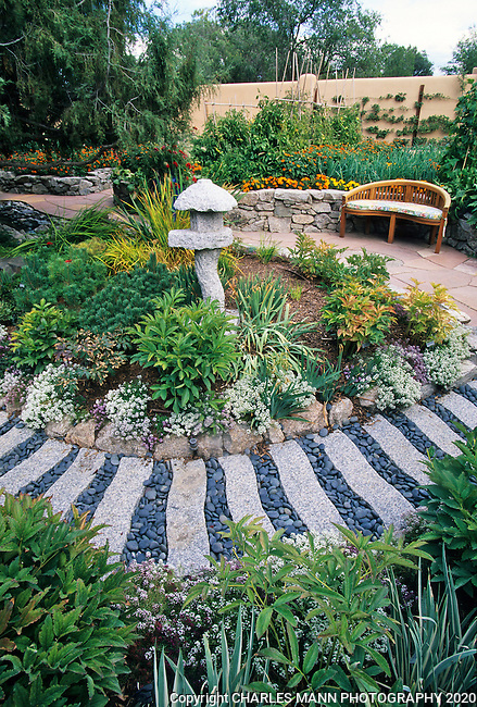 Susan Blevins of Taos, New Mexico, created an elaborate home garden featuring containers, perennial beds, a Japanese themed path and a regional style that reflectes the Spanish and pueblo architecture of the area. A path made from granite and river rock echoes the Japanese inflection of a Japanese stone latnern.
