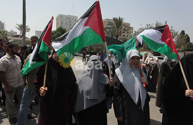 Palestinians hold national flags during a protest to support the Palestinian parliament, Aziz Dweik, in front of the Legislative Council in Gaza City on June 19, 2014. Israeli forces raided Hebron and detained speaker of the Palestinian parliament, Aziz Dweik, along with five other parliamentarians during in an operation to locate three Israeli teens in the West Bank. Photo by Ashraf Amra