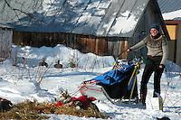 Sigrid Ekran holds Robert Sorlie's sled while Sorlie prepares to depart Grayling. Photo by Jon Little.
